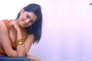 Parvati-Vaze-Sitting-On-A-Chair-In-Orange-Top-And-Blue-Jeans-Smiling