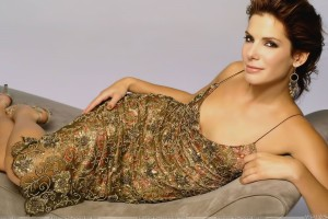 Sandra Bullock Smiling Laying in Golden Designing Dress Photoshoot